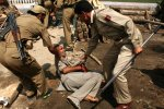 Pic11-09-8-07-09-Indian policemen beat an elderly person who